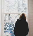 Picture of a woman's back who is staring out the window.