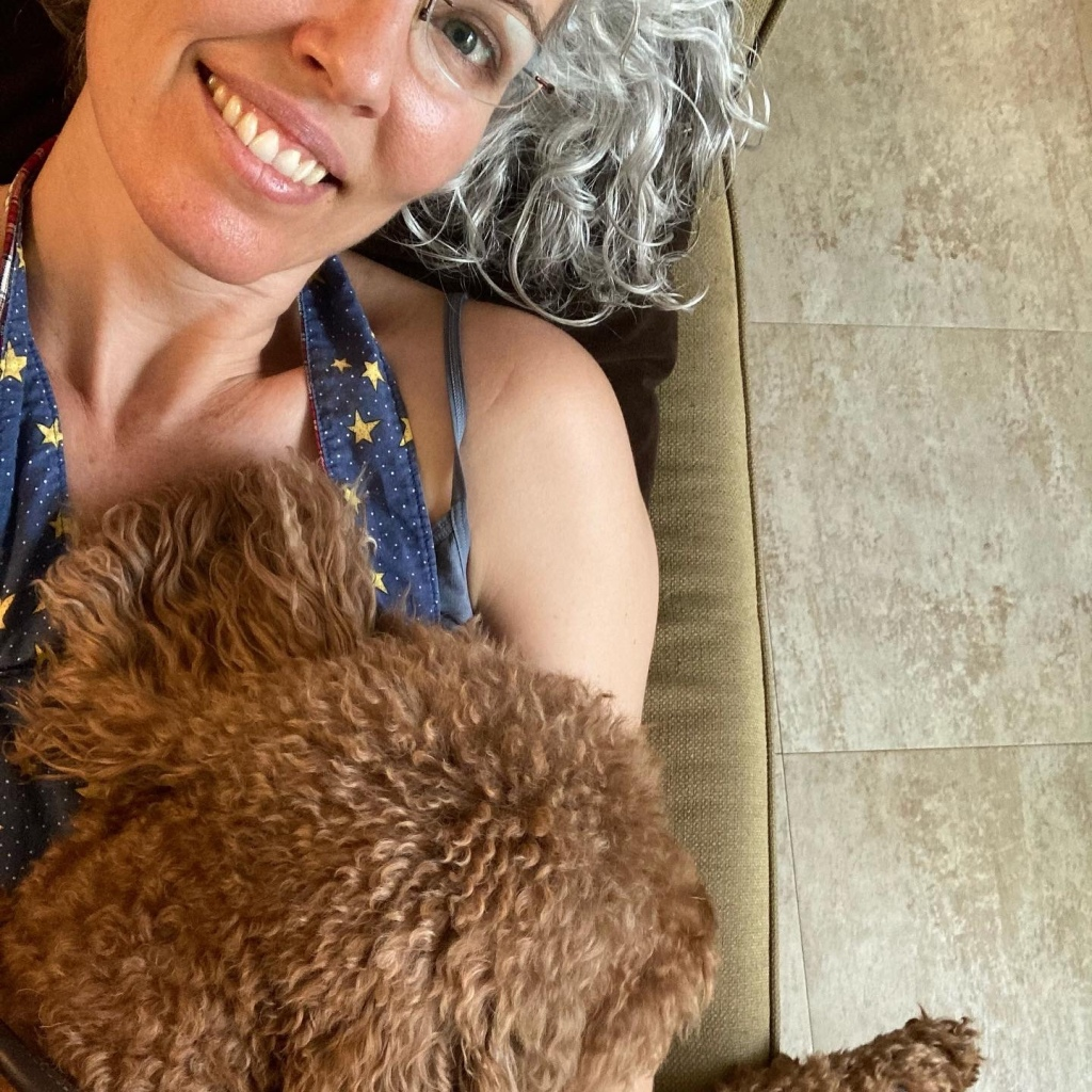 Picture of the author laying on the couch with her dog lying on top of her. The author smiles at the camera and is wearing an apron.